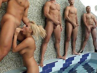 Myra Lyon is on her knees and goes around sucking hard cocks